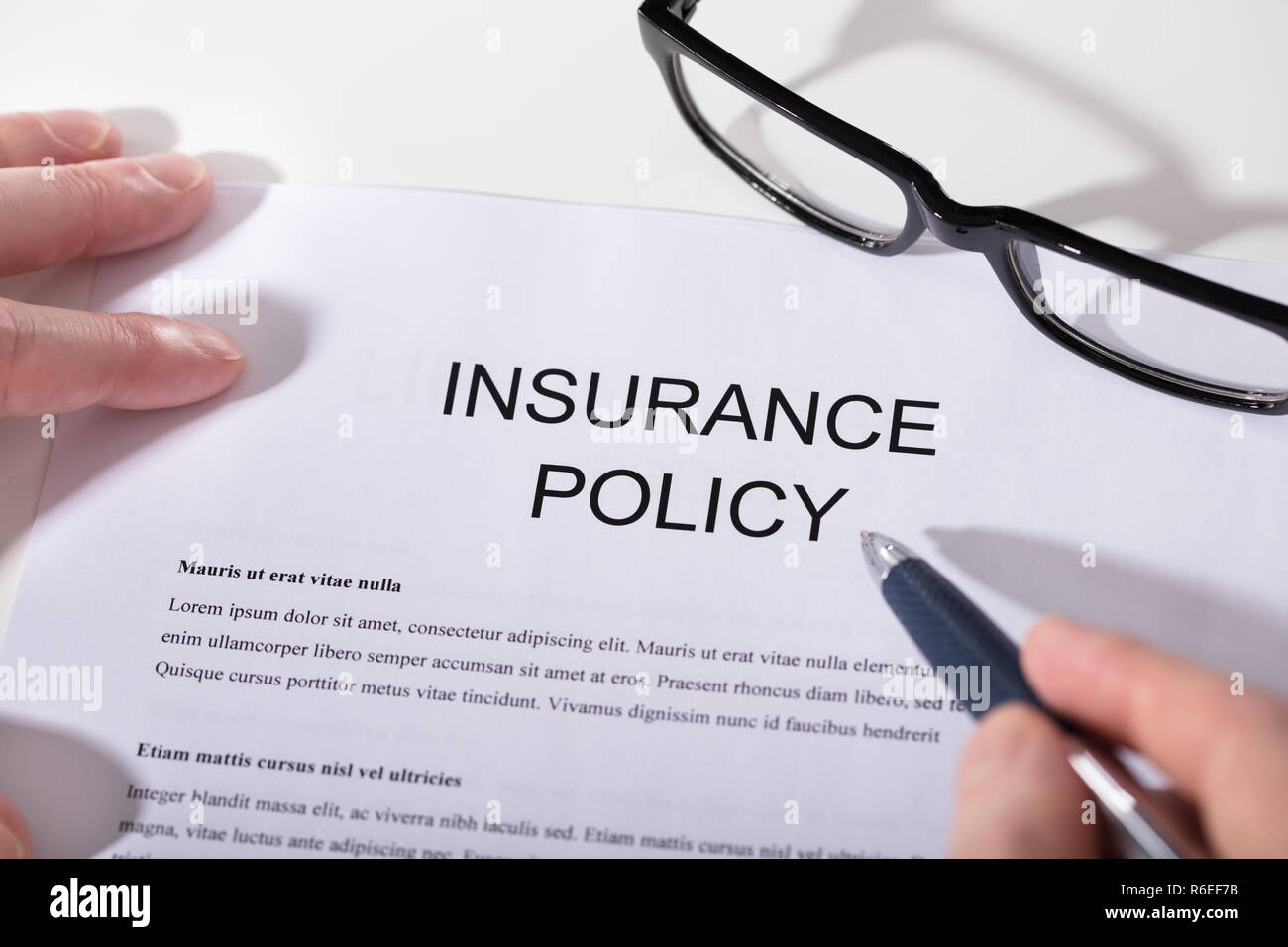Person's Hand Over Insurance Policy Form - Stock Image