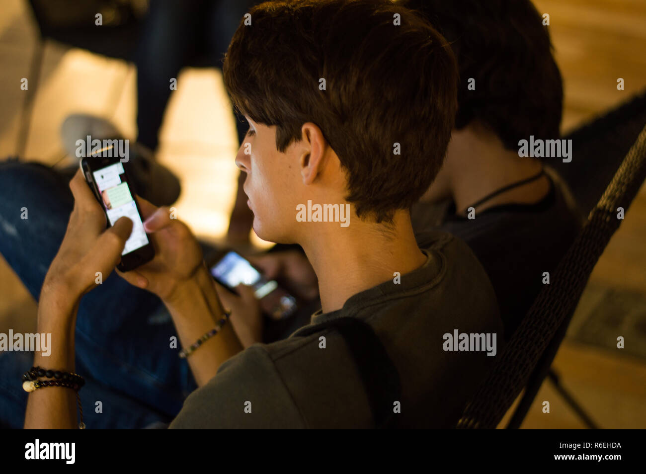 Engrossed teens scrolling through their mobile phones, ignoring each other - Stock Image