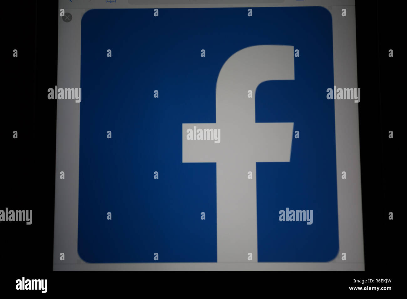 Facebook, online social media and social networking service company, logo is shown on Apple iPad Air device screen - Stock Image