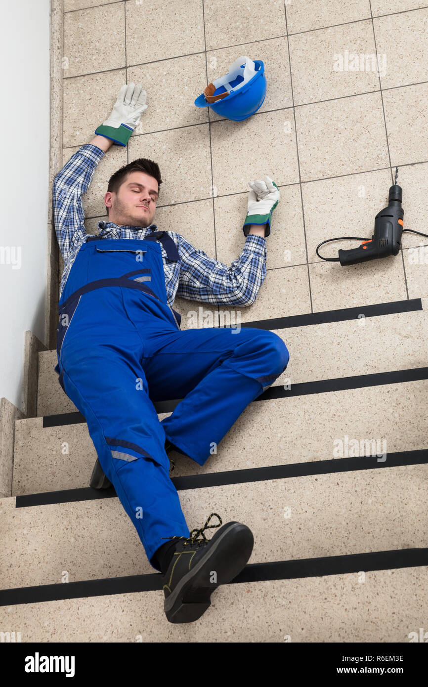 Handyman Lying On Staircase - Stock Image