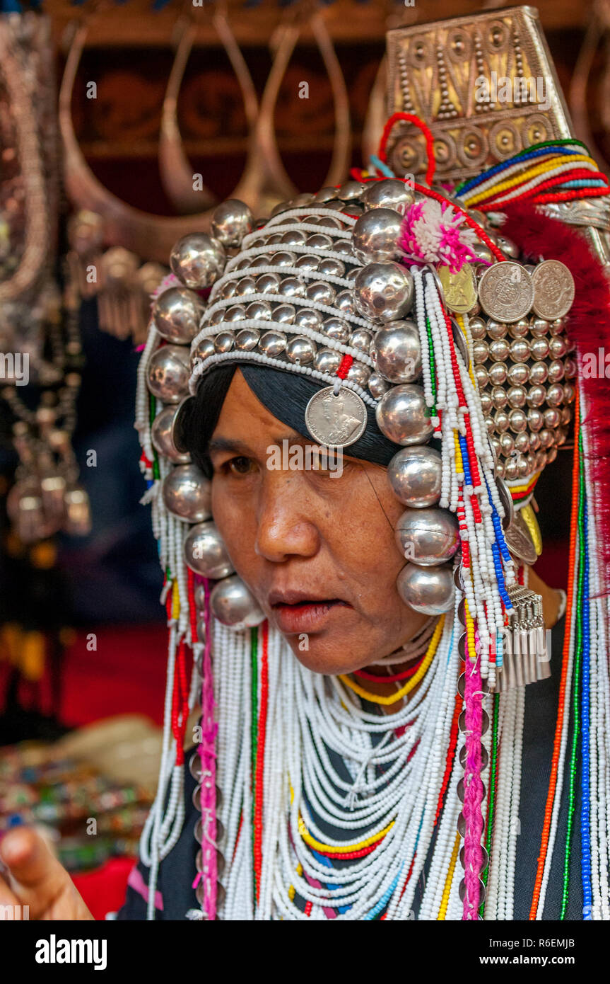 Akha Tribeswoman In Traditional Clothing And Wearing An Ornate Headdress, Chiang Mai, Thailand - Stock Image