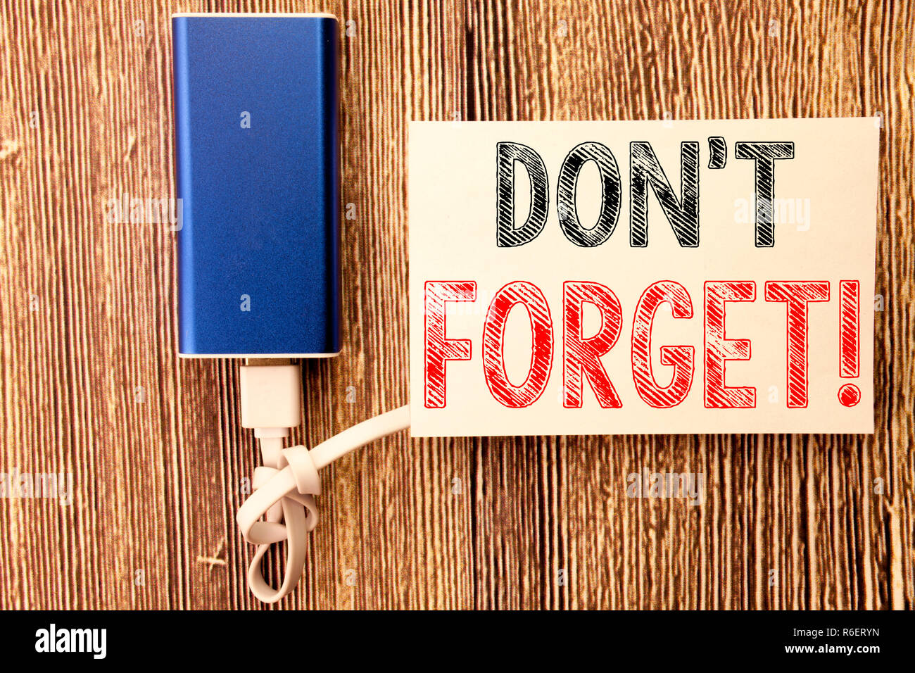 Conceptual hand writing text caption inspiration showing Do Not Forget. Business concept for Reminder Message written on sticky note old wood wooden background with power bank - Stock Image