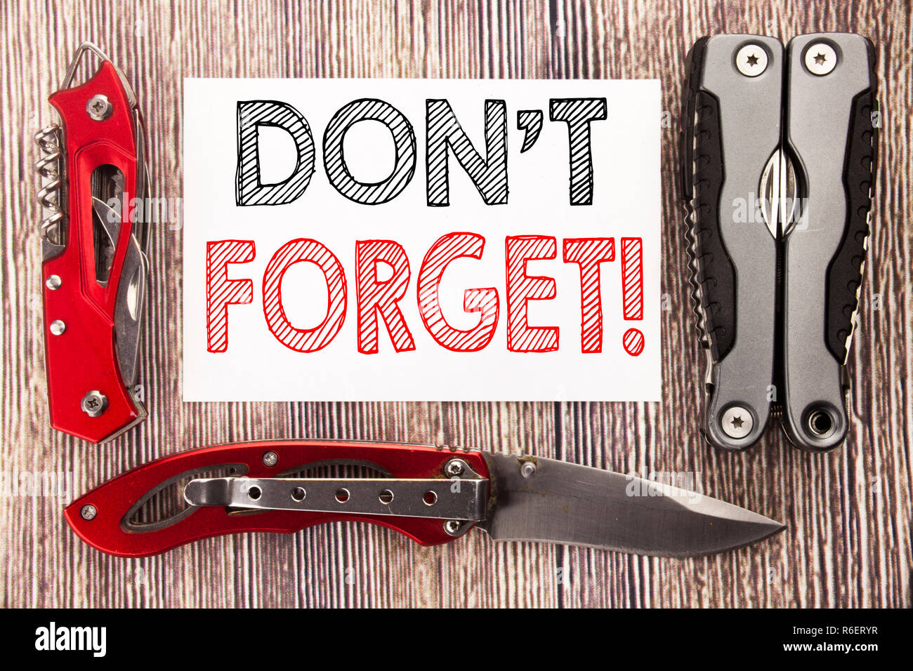 Conceptual hand writing text caption inspiration showing Do Not Forget. Business concept for Reminder Message Written on sticky note wooden background with pocket knife - Stock Image