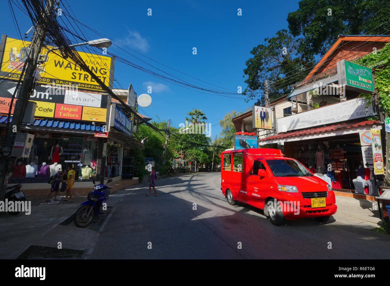 A songthaew, a small passenger van or bus on its way through the beach road in Kamala, Phuket, Thailand - Stock Image
