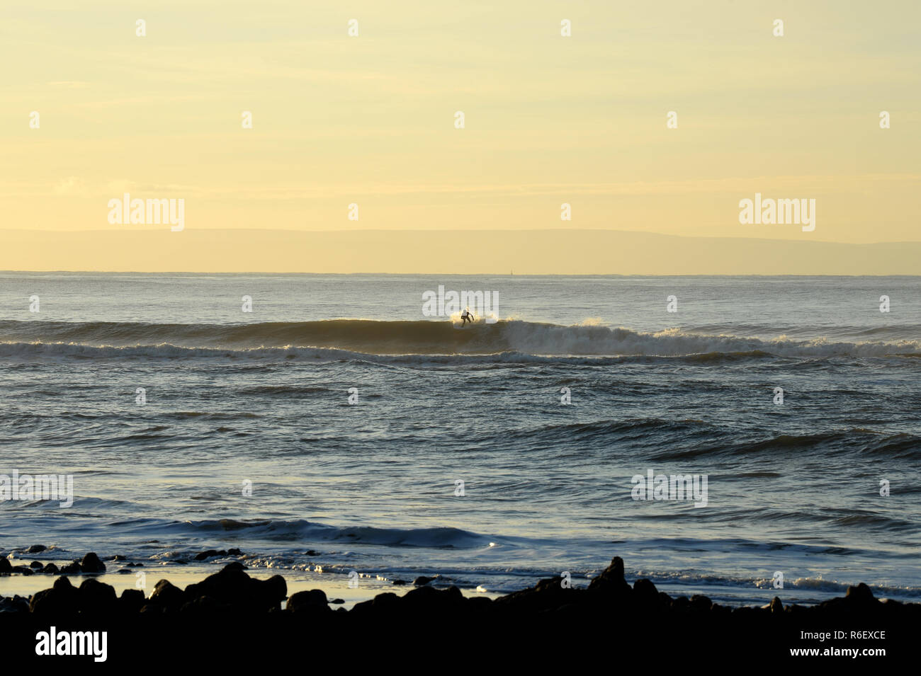 Surfer on crest of wave at Crab Island, Gower Stock Photo