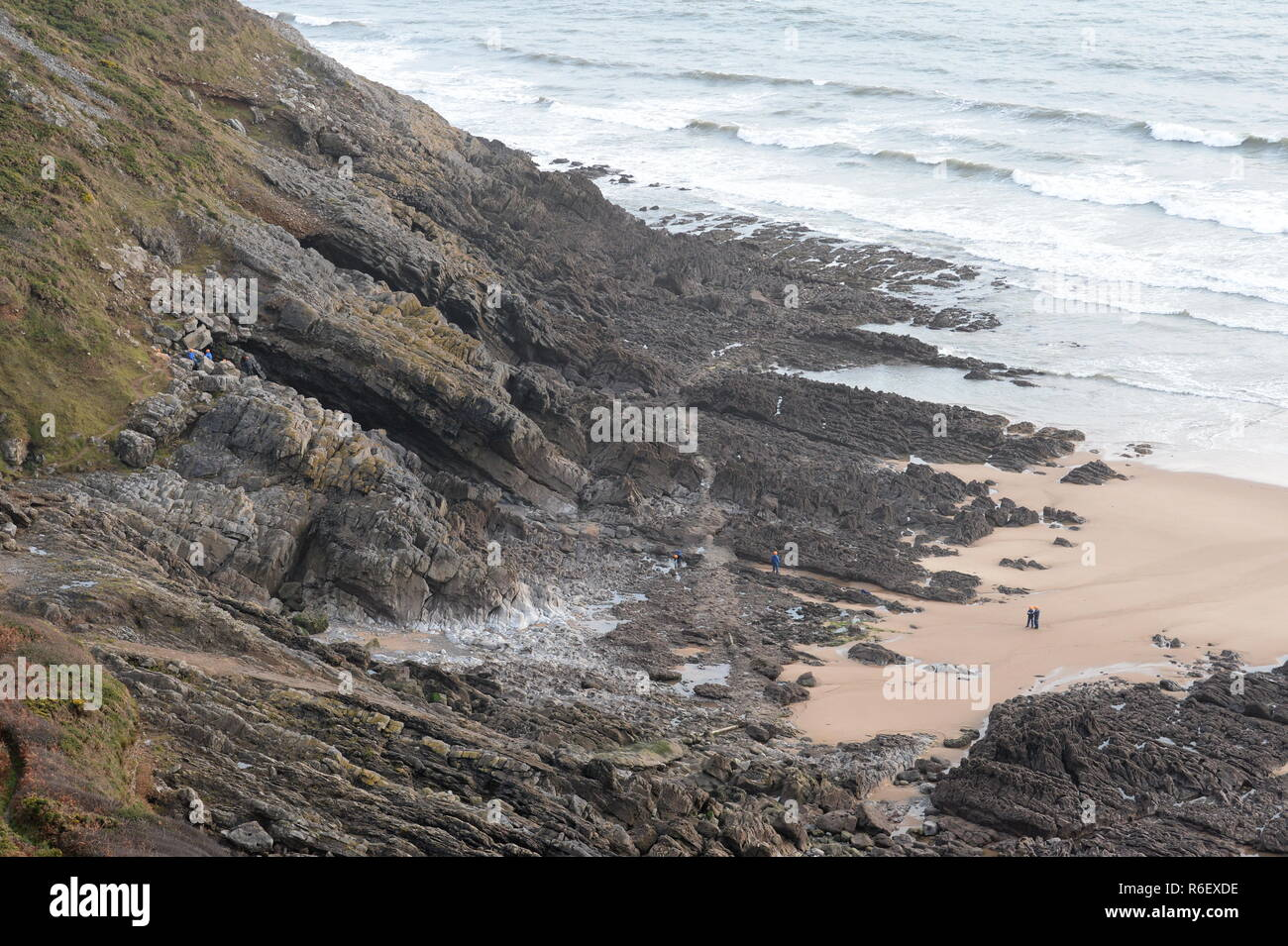 Geology students investigate one of the many cliffs and caves of the Gower at East Cliff ,High Tor, Southgate, Gower ,Wales Stock Photo