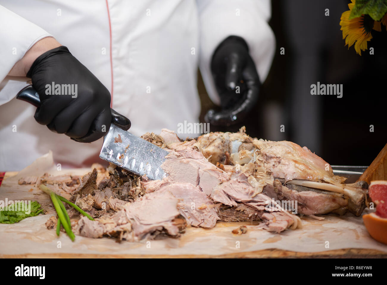 Chief cook cuts into pieces freshly cooked pork thigh, process close up. Show at restaurant - Stock Image