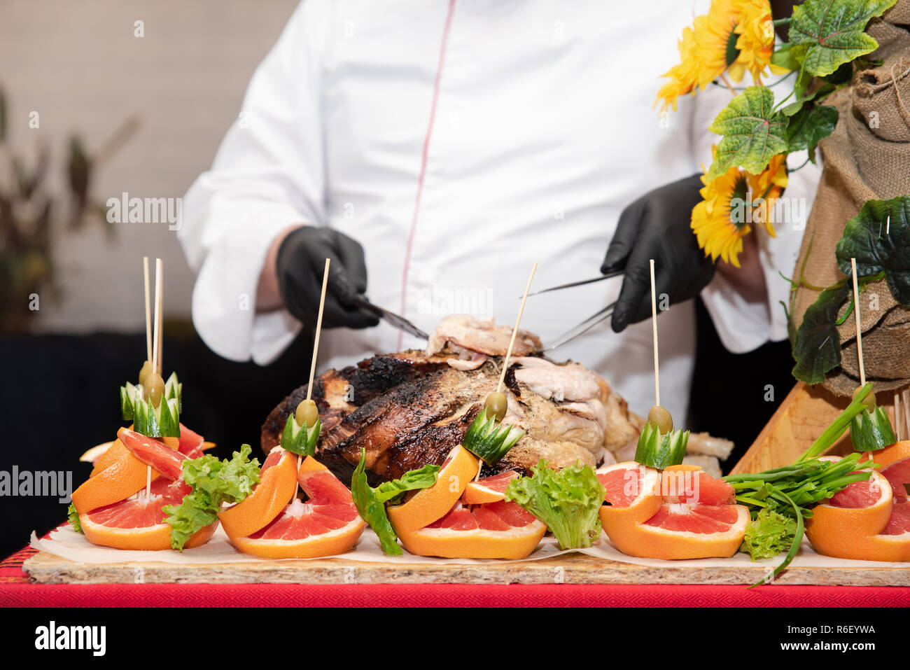 Show at restaurant: chief cook cuts into pieces freshly cooked pork thigh, process close up. Decorations of fruits and vegetables on the table, catering - Stock Image