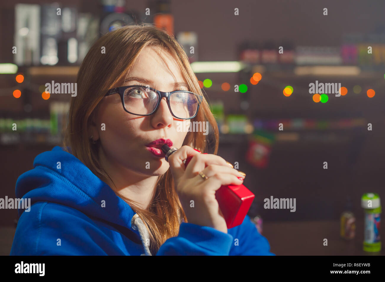 beautiful young woman with glasses smoking electronic cigarette. girl in a blue sweater brings to his lips red box mod, sitting indoors vape shop cafe - Stock Image