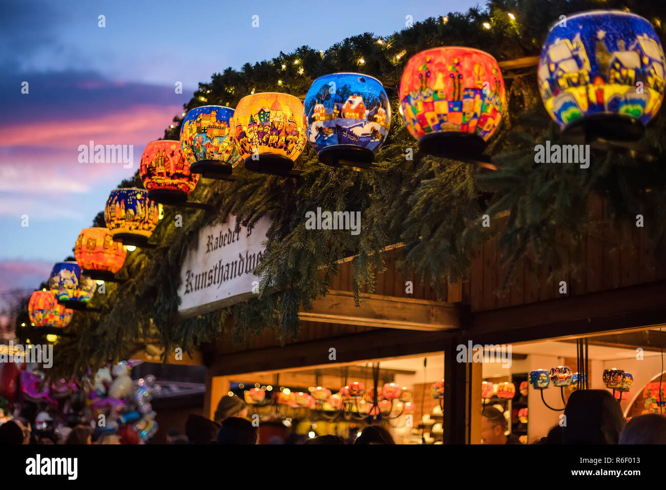 Vienna, Austria - December 24, 2017. Lighting painted glass candle holders with colorful ornaments in kiosk at Viennese Christmas market. Close view o - Stock Image