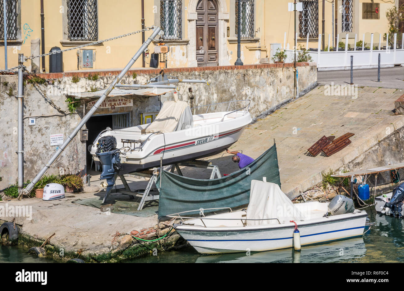 Man restoring vintage wooden rowing boat in the Venice quarter of Livorno, Tuscany, Italy - Stock Image