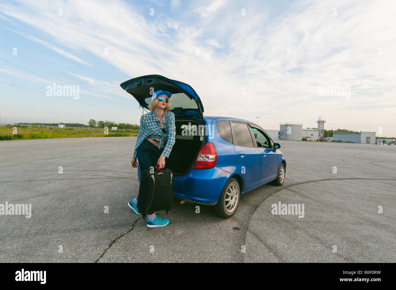 young slim woman dressed in blue checked shirt, cap and jeans, Will depart at dawn on summer day on freedom trip with black travel suitcase. Takes out a bag from the car - Stock Image