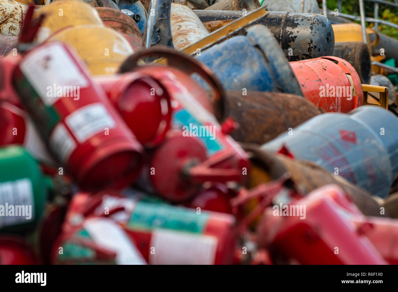 Old extinguisher and gas bottles on scrap yard - Stock Image