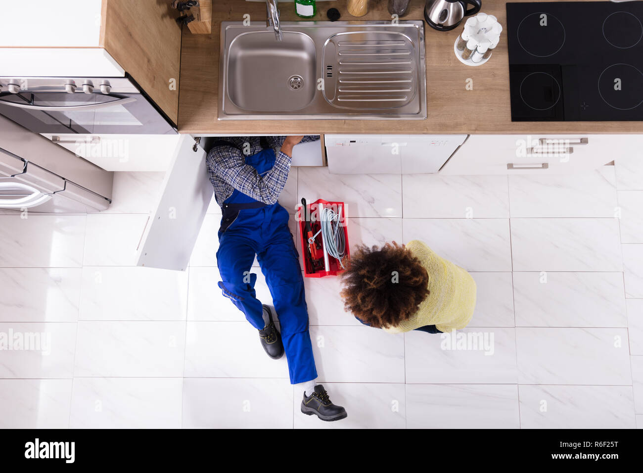 Plumber Repairing Sink In Kitchen - Stock Image