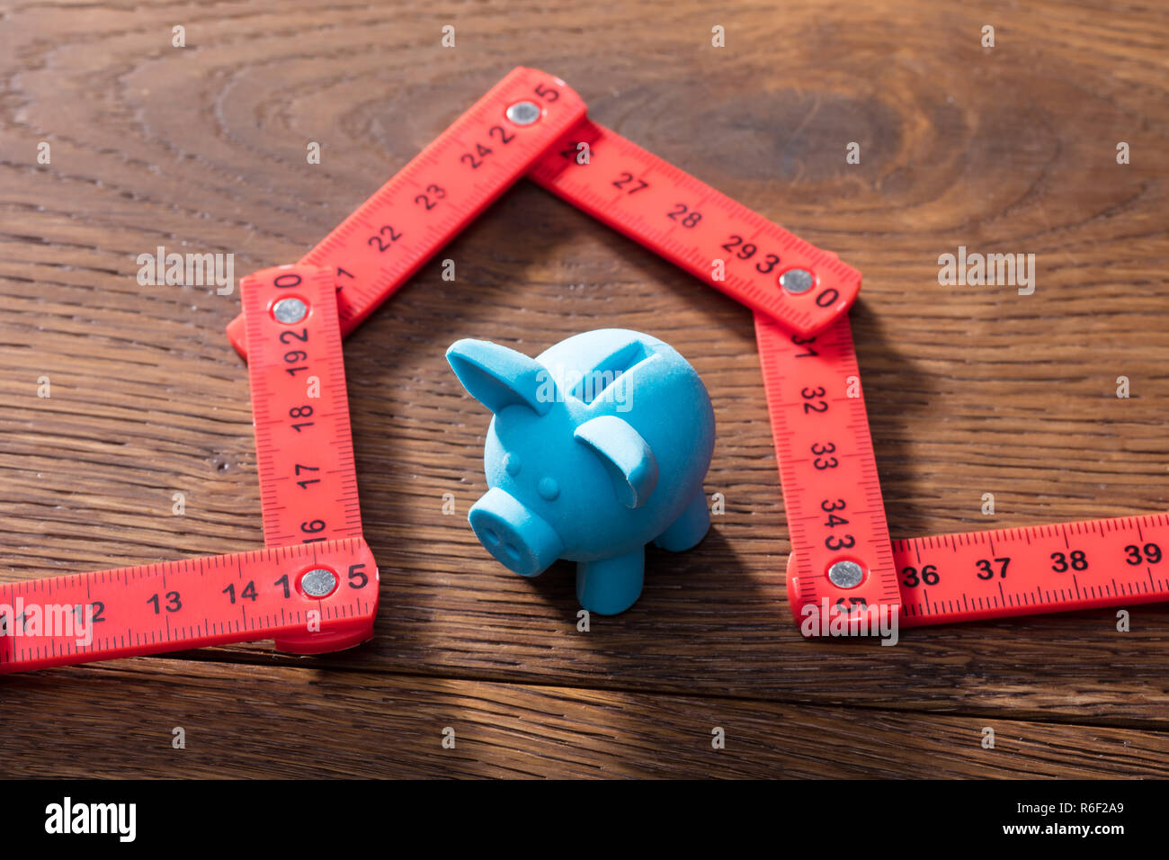 Piggybank Under The House Made With Measuring Tape - Stock Image