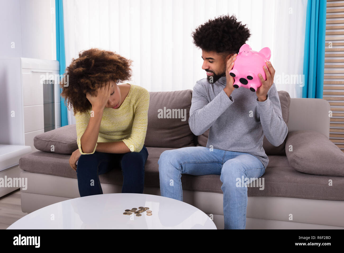 Woman Looking At Piggybank Raised By Man - Stock Image
