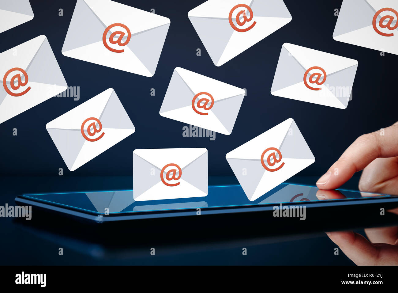 Newsletter and email marketing concept. Hand touching tablet showing email icons on dark background. - Stock Image