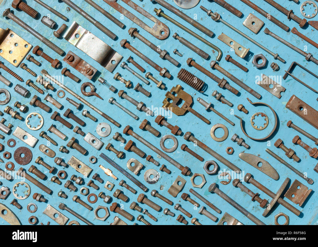 set of old rusty metal screws, nuts and bolts on a blue background. Flat lay, top view Stock Photo