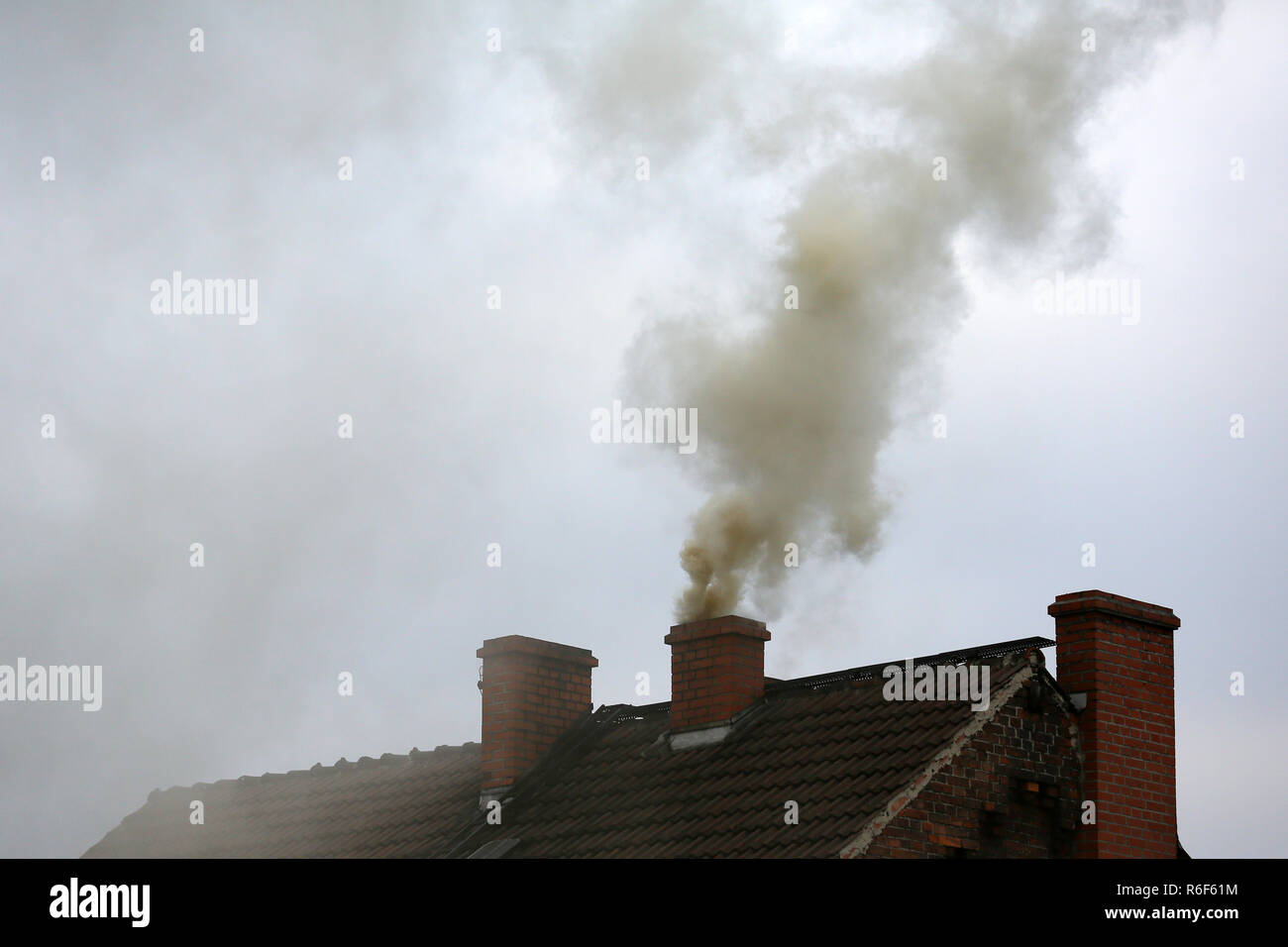 Smoke from the chimney of a house fueled with coal Stock Photo