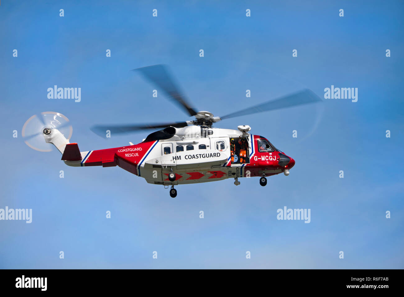 Horizontal close up of a coastguard helicopter in flight. Stock Photo