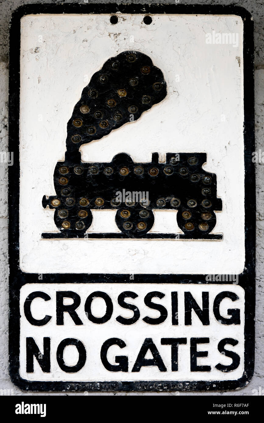 Vertical close up of an old black and white roadsign. - Stock Image