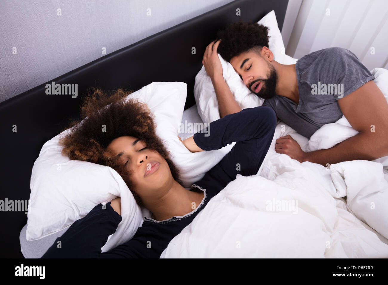 Woman Covering Her Ears While Man Snoring In Bed - Stock Image