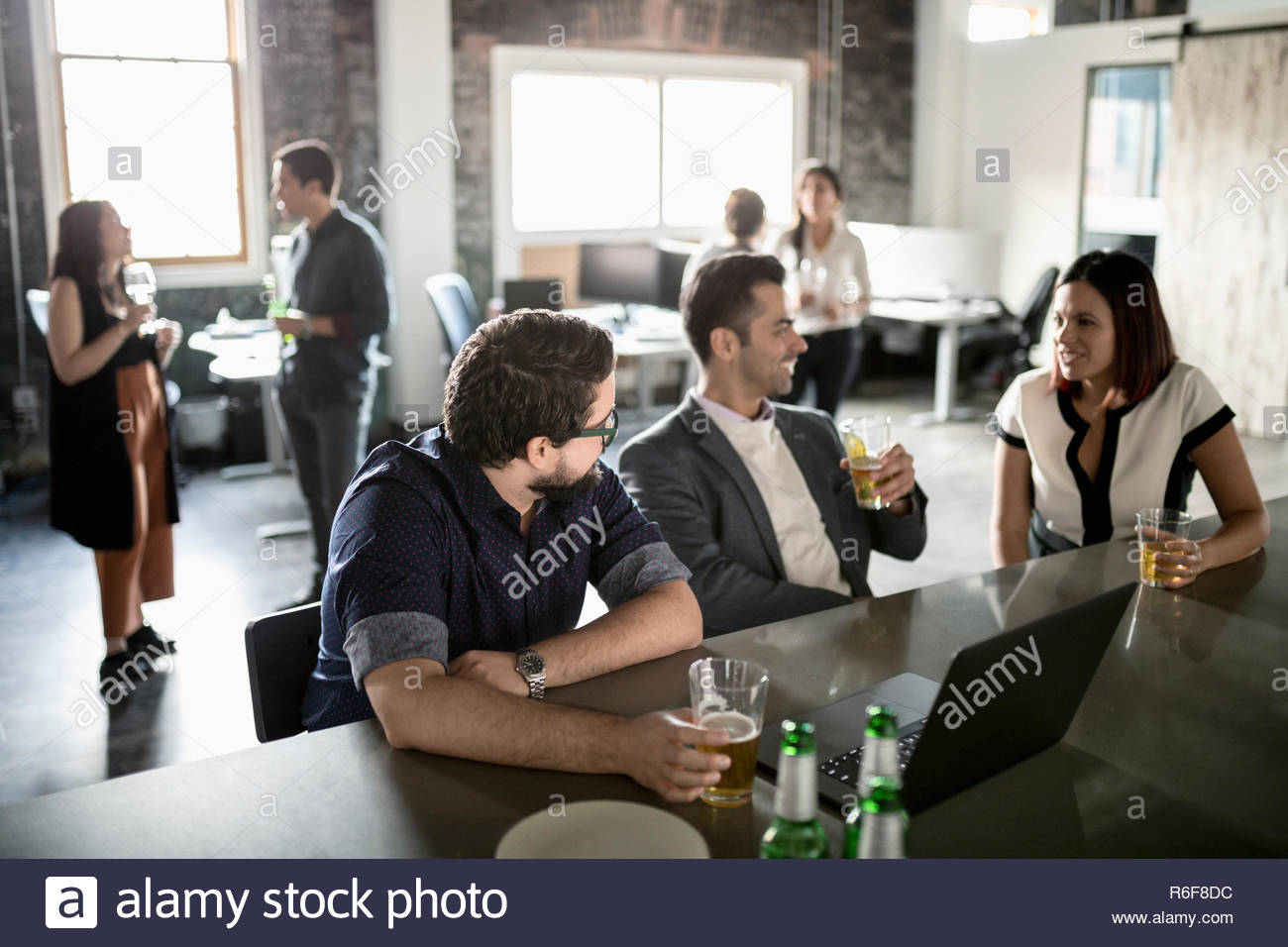 Creative business people drinking beer in loft office - Stock Image