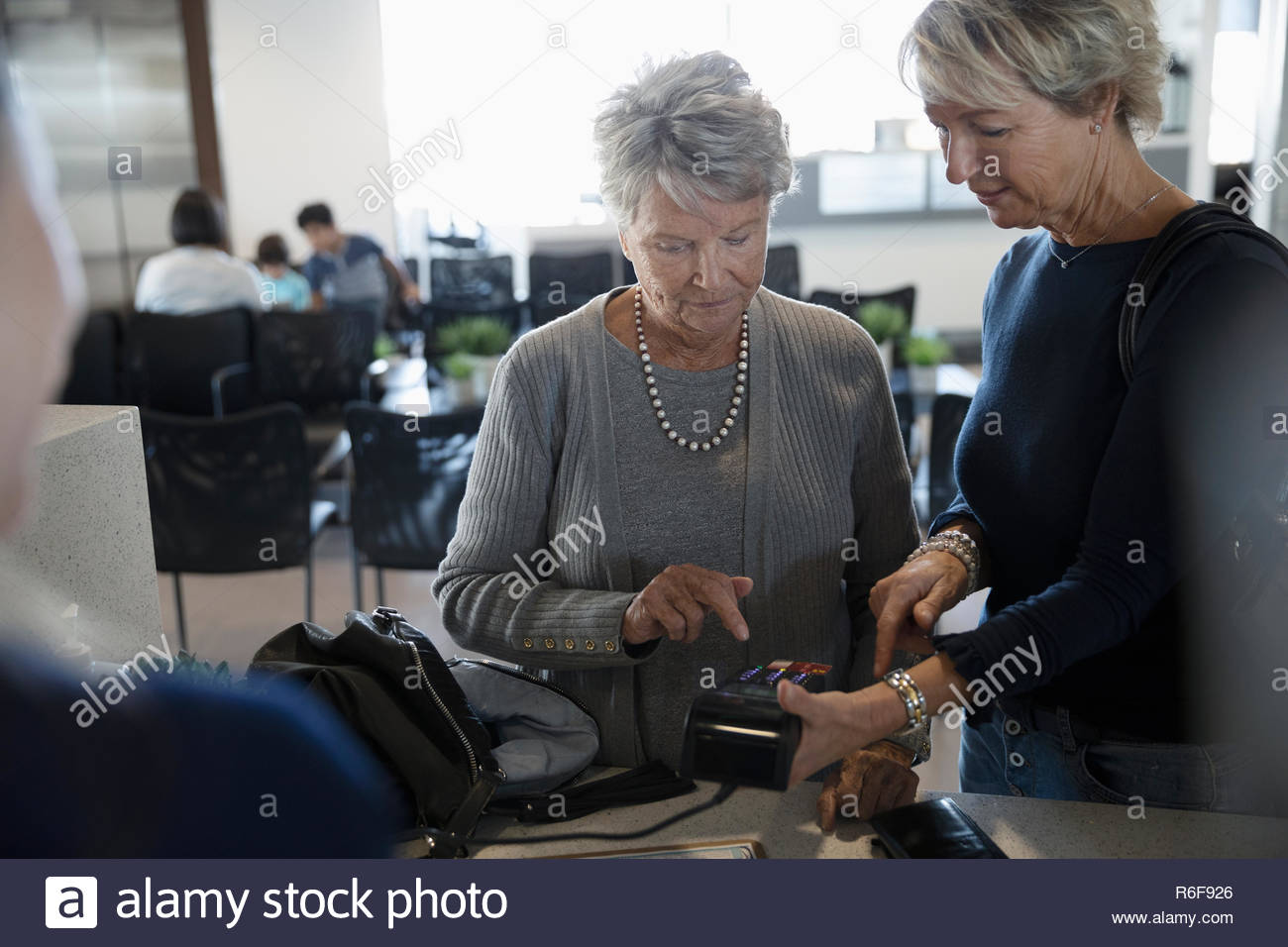 Woman helping senior mother pay at clinic check-in - Stock Image