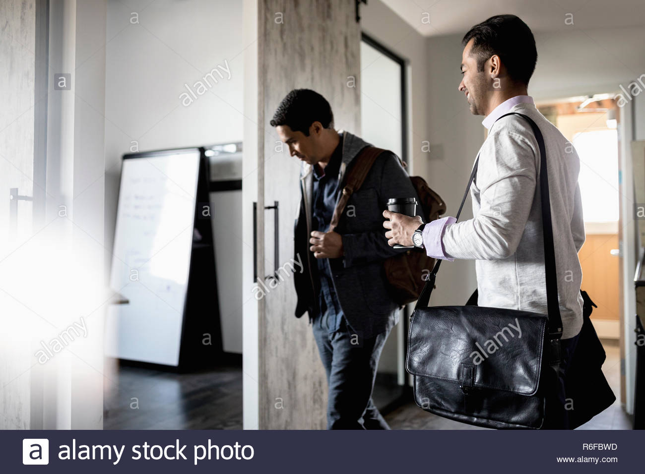 Creative businessmen arriving at office - Stock Image
