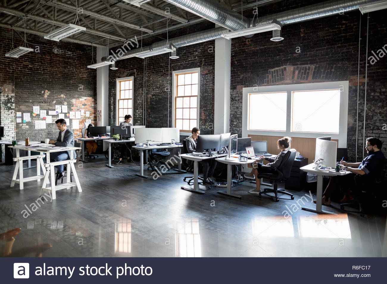 Creative business people working at desks in open space loft office - Stock Image