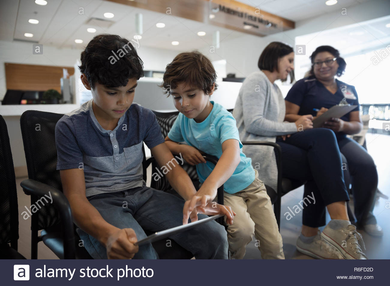 Boys using digital tablet while mother and nurse talk in clinic waiting room Stock Photo