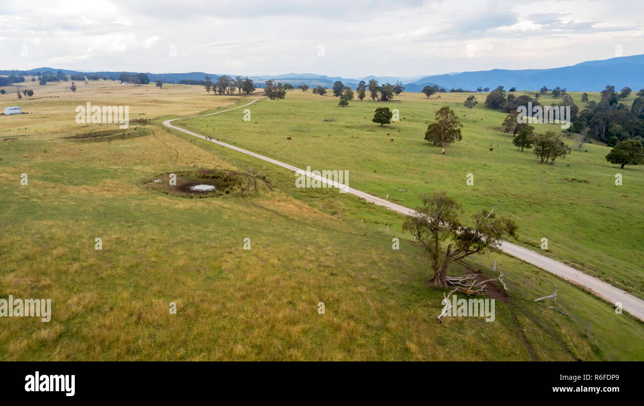 aerial view of country road running in the midst of green paddocks with mountains in the background Stock Photo