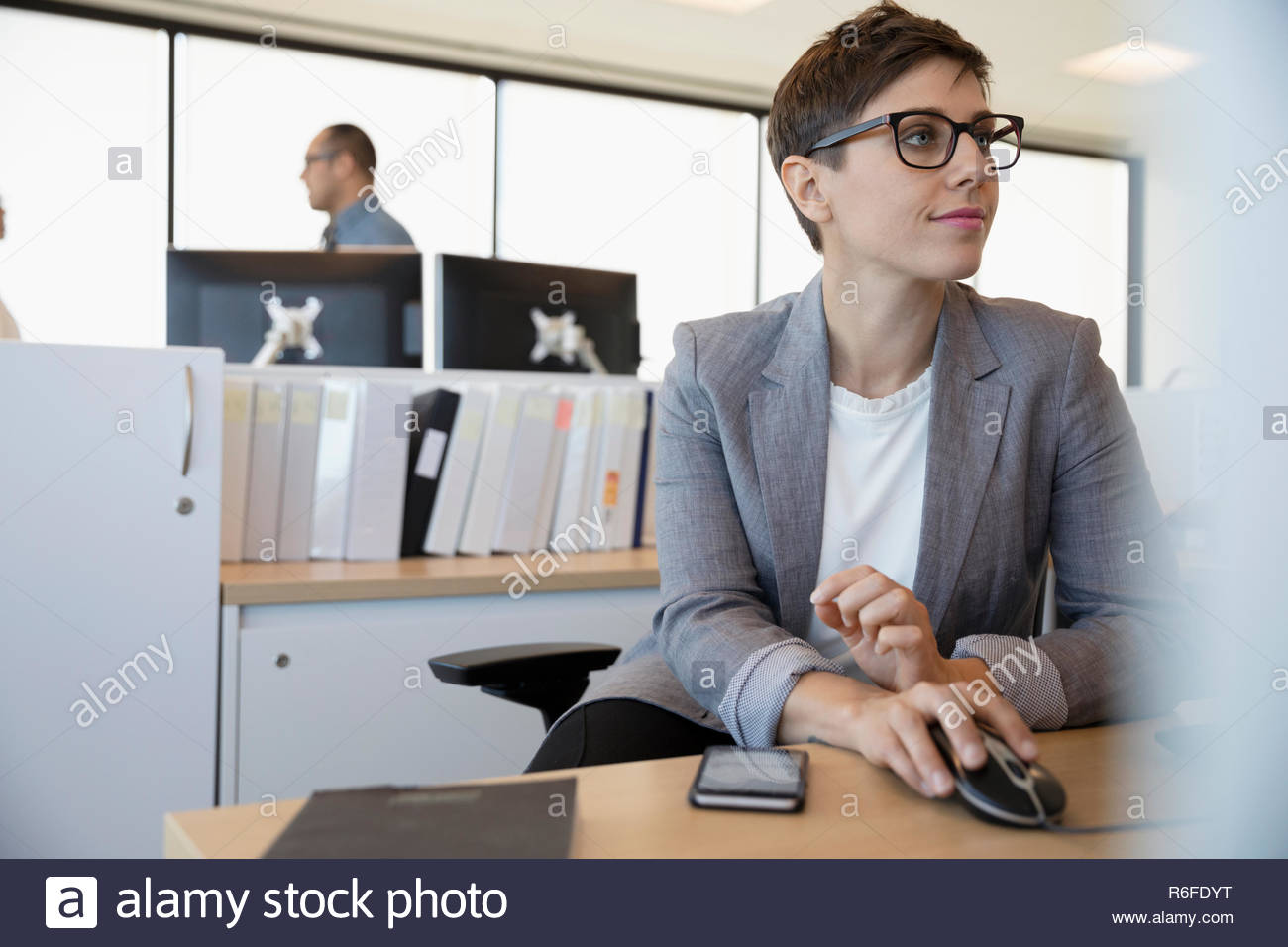 Businesswoman working in office cubicle - Stock Image