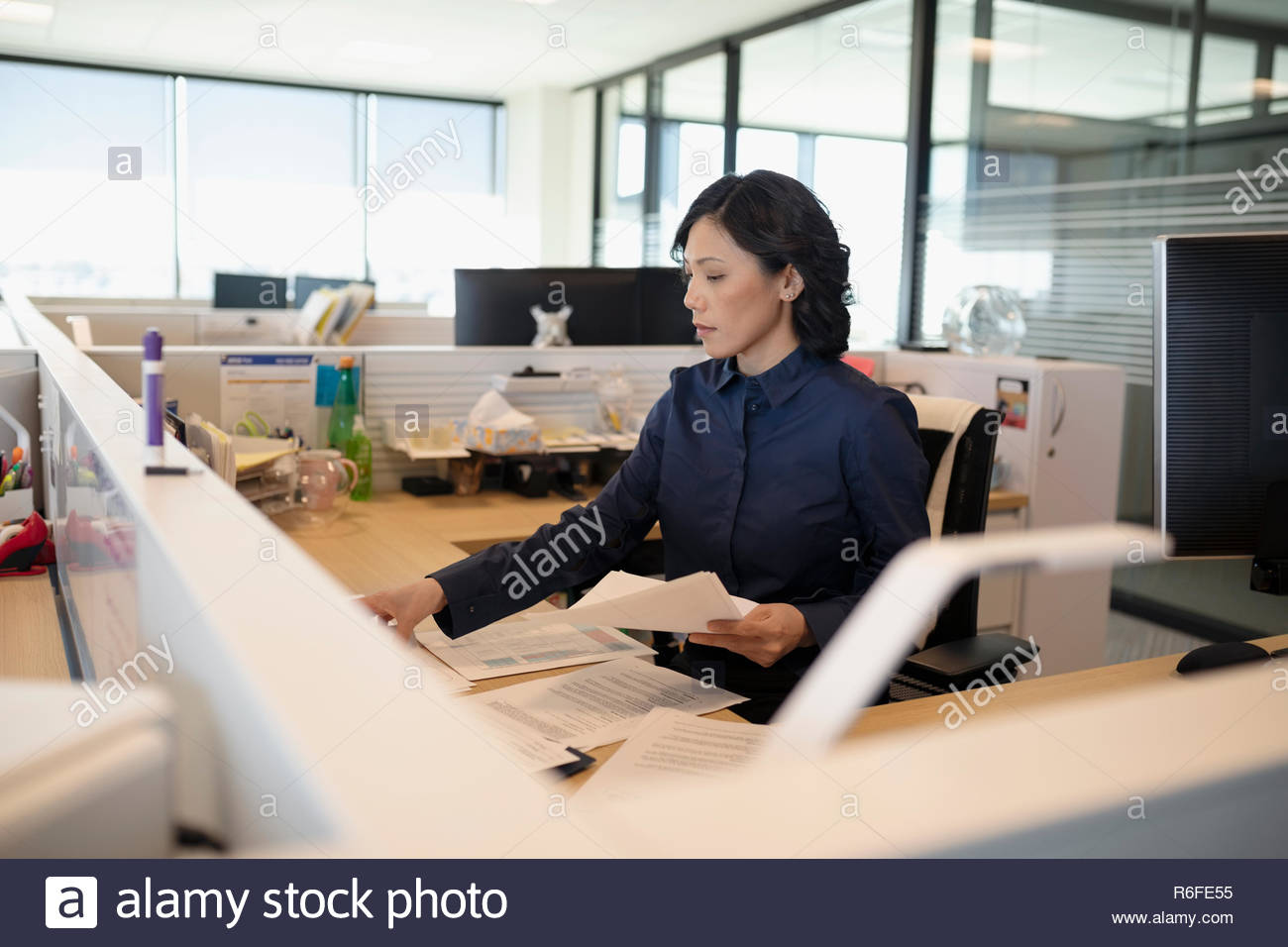 Businesswoman sorting paperwork in office cubicle - Stock Image