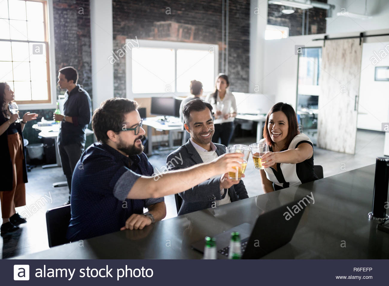 Creative business people toasting beer glasses in loft office - Stock Image