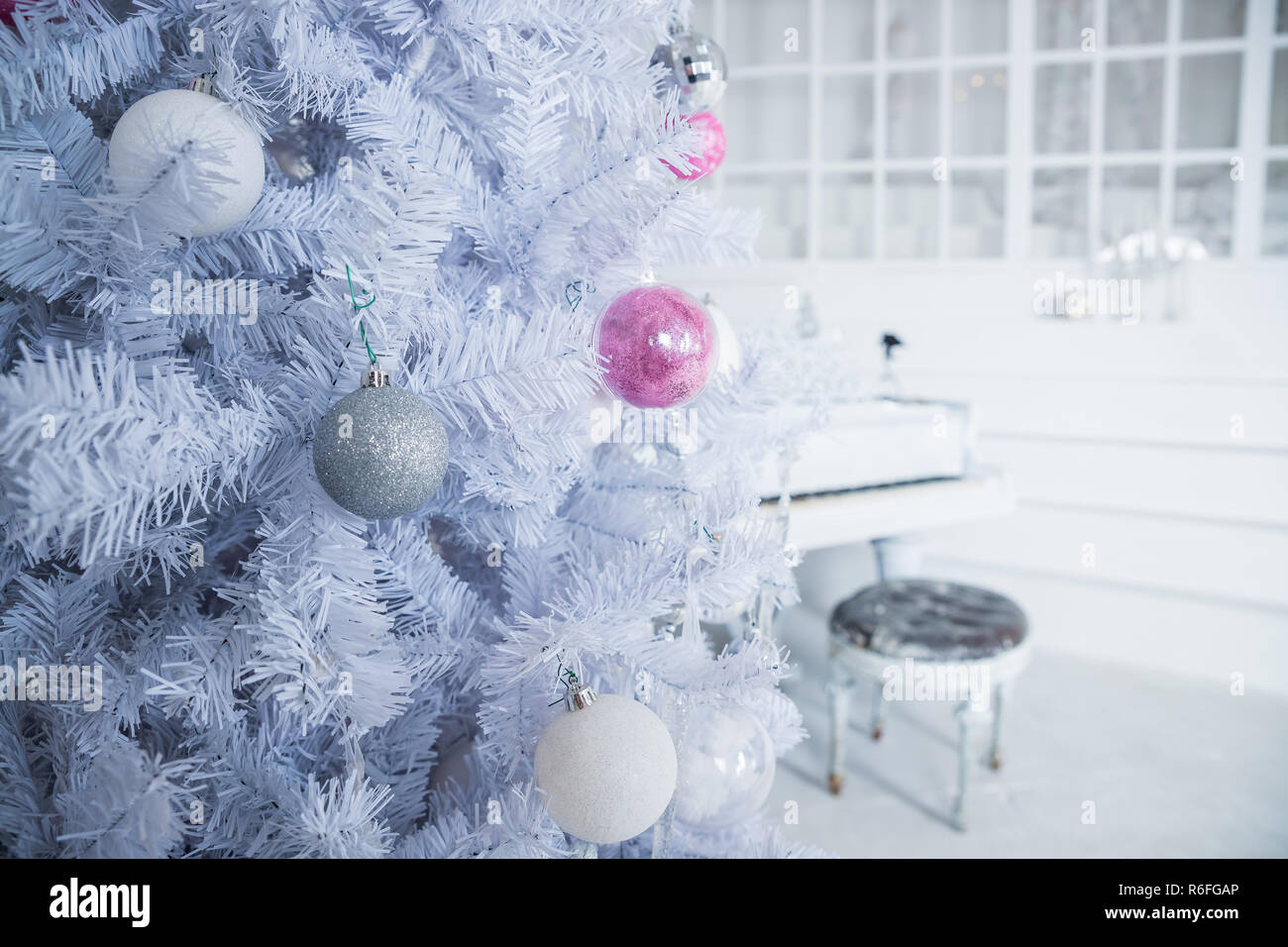 White Christmas Tree Decorated With Silver And Pink Ornaments At The Piano Background Winter Scene New Year Decoration Xmas Interior Design Includes Decorated Christmas Tree Selective Focus Classical White Hall Stock Photo Alamy