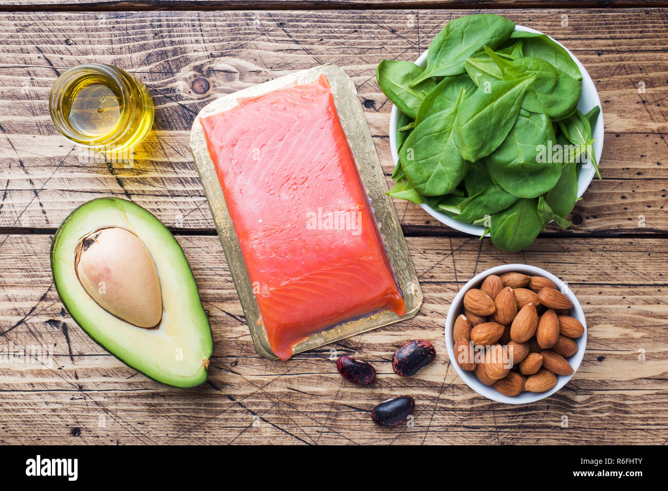Concept Healthy food antioxidant products: fish and avocado, nuts and fish oil, grapefruit on wooden background - Stock Image