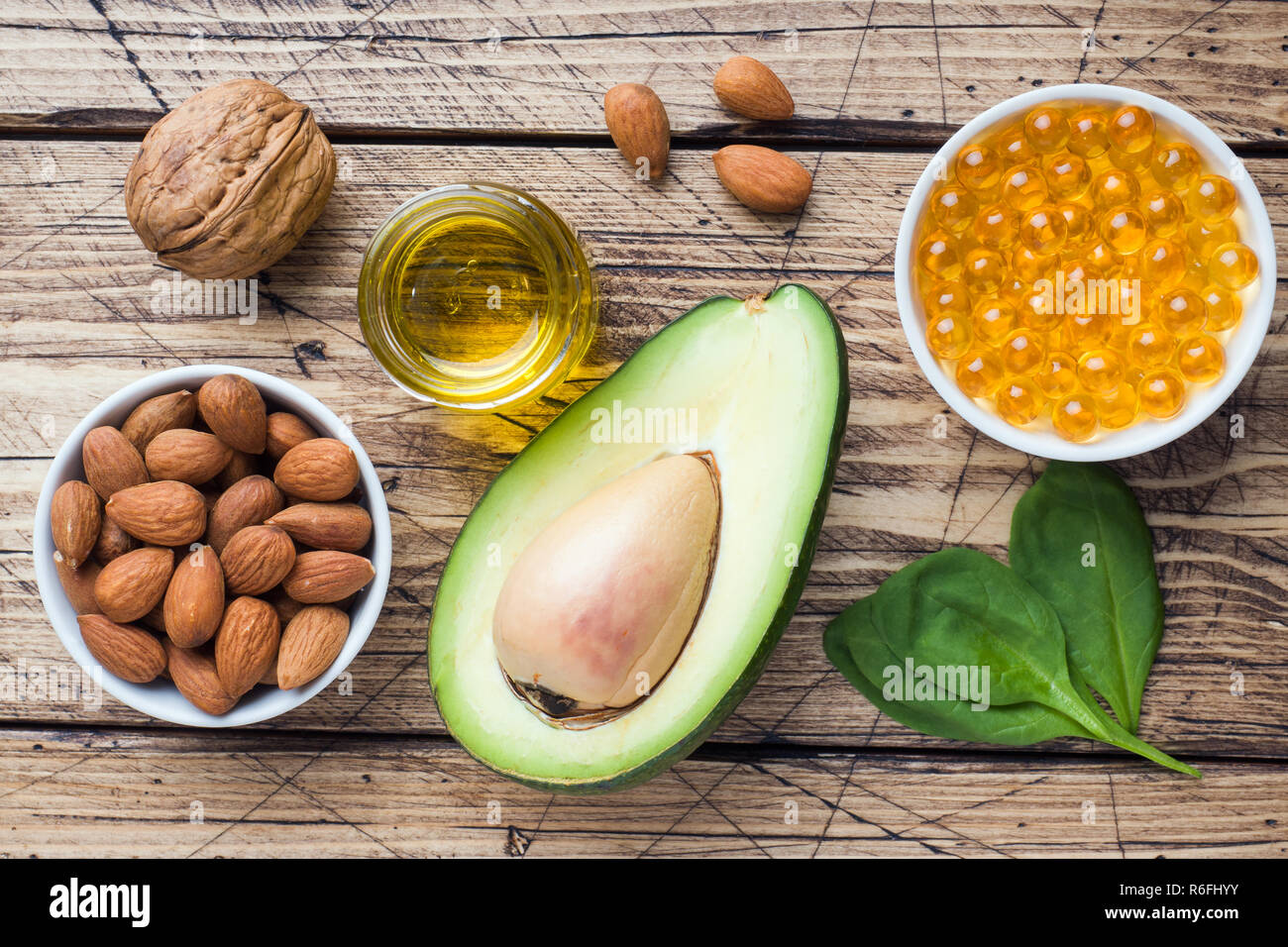 Concept Healthy food antioxidant products avocado, nuts and fish oil, grapefruit on wooden background - Stock Image