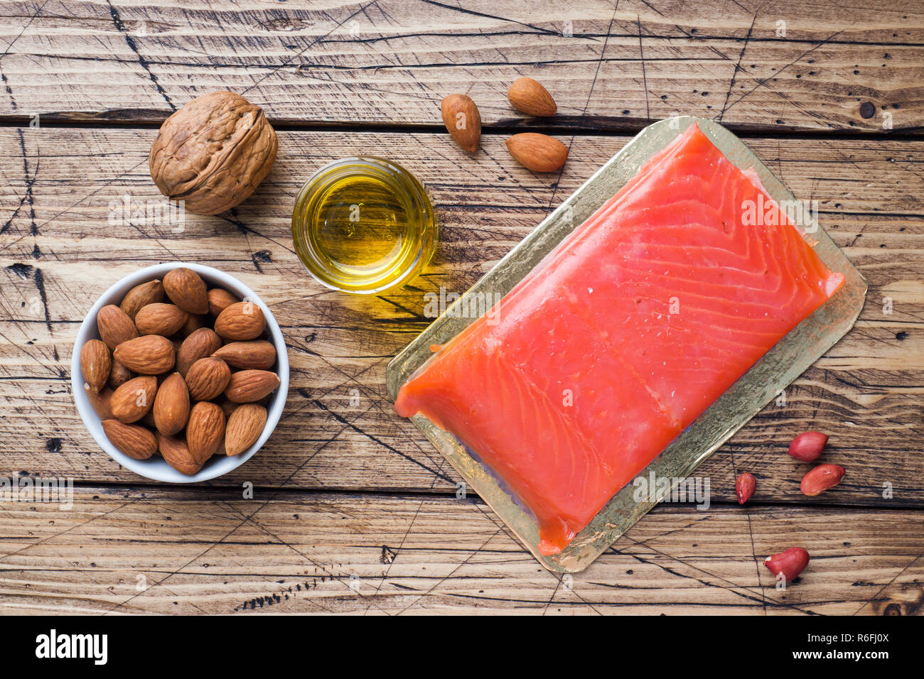 Concept Healthy food antioxidant products: fish nuts and oil on wooden background - Stock Image