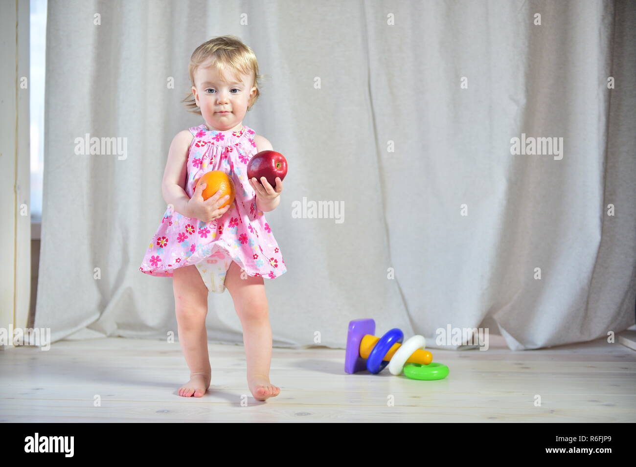 c70b112e9ff Pretty little girl in a pink dress with red apple and orange in hands on a  light background