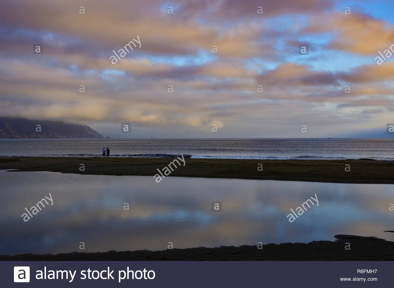 A couple is enjoying sunset at the Pacific coast of Crescent City in California - Stock Image