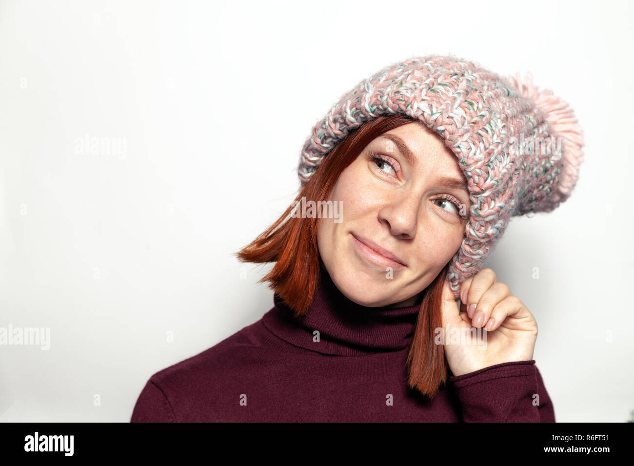 Isolated Portrait Of Beautiful Young Redhead Girl In Purple Sweater And Pink Knitted Hat With Pompon Dressed Sideways Smiling On White Background In S
