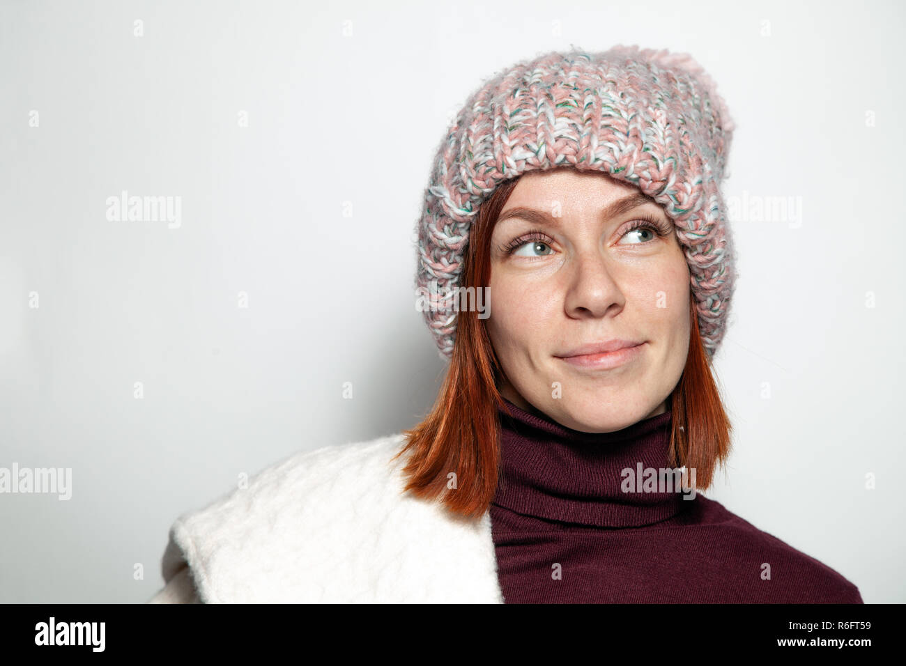 Isolated Portrait Of Beautiful Young Redhead Girl With Green Eyes White And Purple Sweater And Pink Knitted Hat With Pompon Dressed Sideways Smiling O
