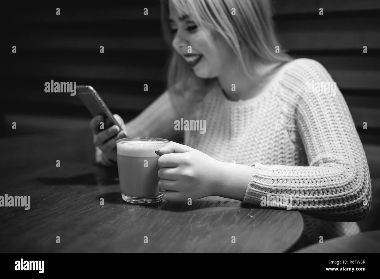 Young blonde woman in a knitted sweater sitting at a table in a cafe with a cup of coffee in her hands, spending time alone, doing internet communication through wifi - Stock Image