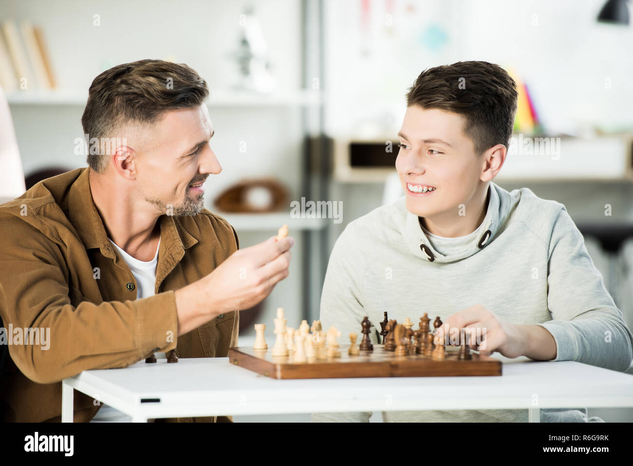 smiling father and teen son playing chess at home and looking at rh alamy com chase at home jobs chase at home