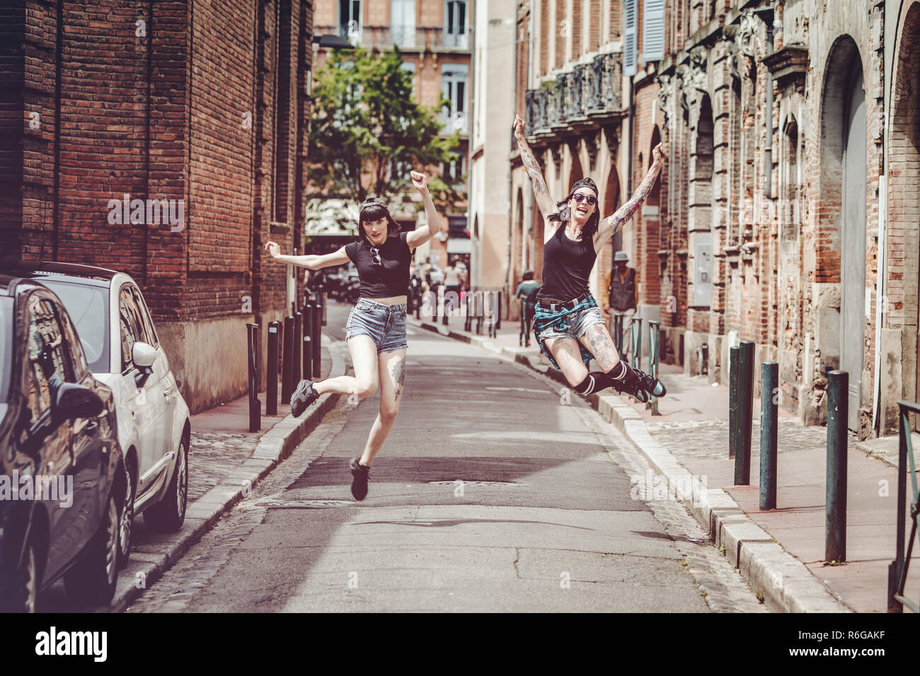 Jumping of two young women on a street in the city center - Stock Image