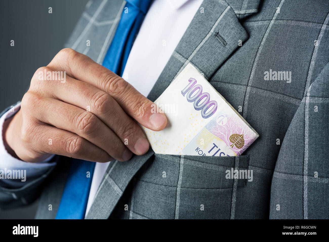 closeup of a young caucasian businessman, wearing an elegant gray suit, putting in or taking off some czech koruna banknotes in the pocket of his jack - Stock Image