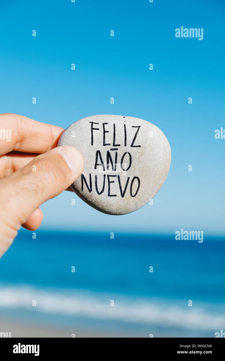 closeup of a young man on the beach, with a stone in his hand, with the text feliz ano nuevo, happy new year written in spanish, and the ocean in the  - Stock Image