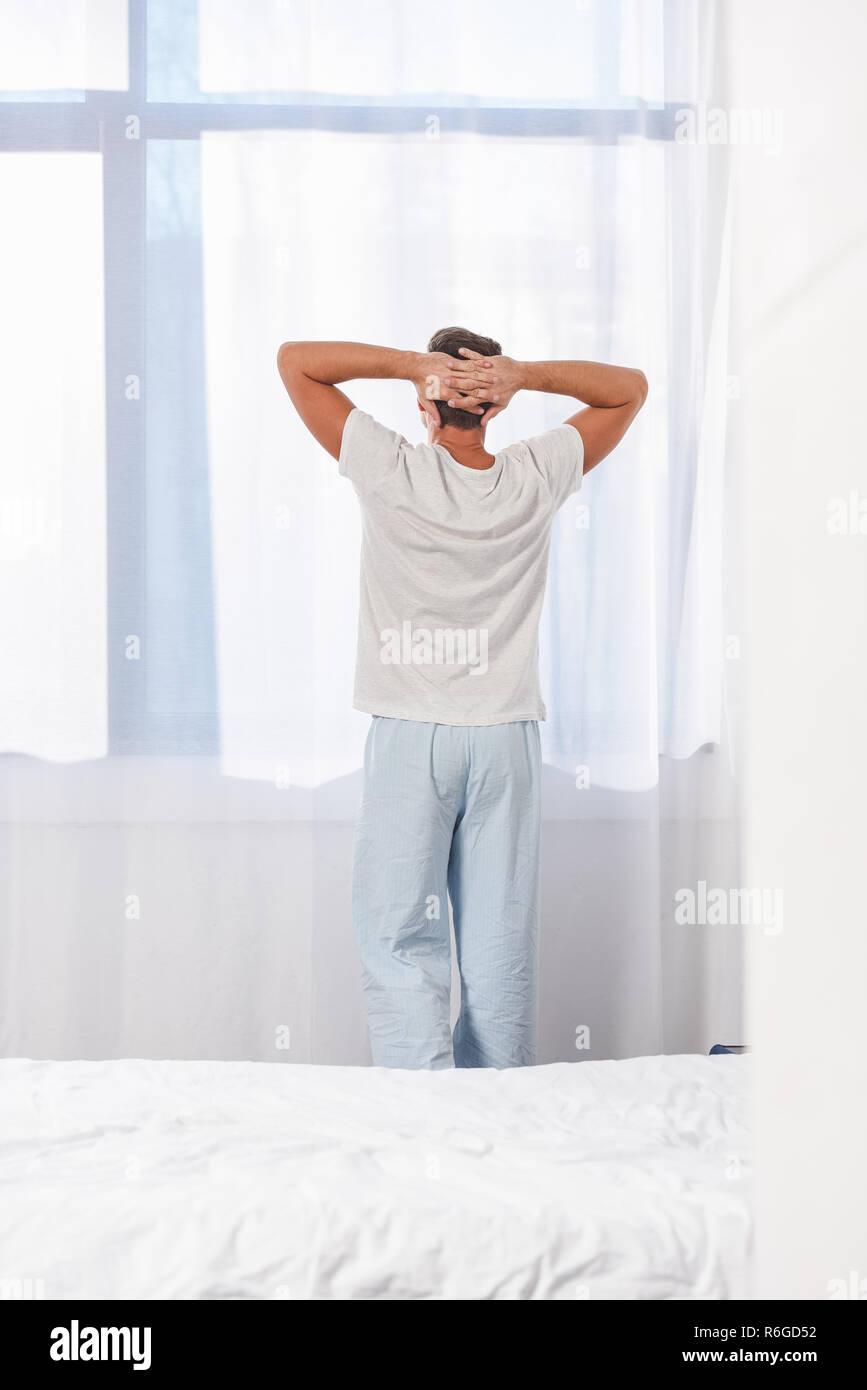 Back view of man standing in sleepwear in room - Stock Image