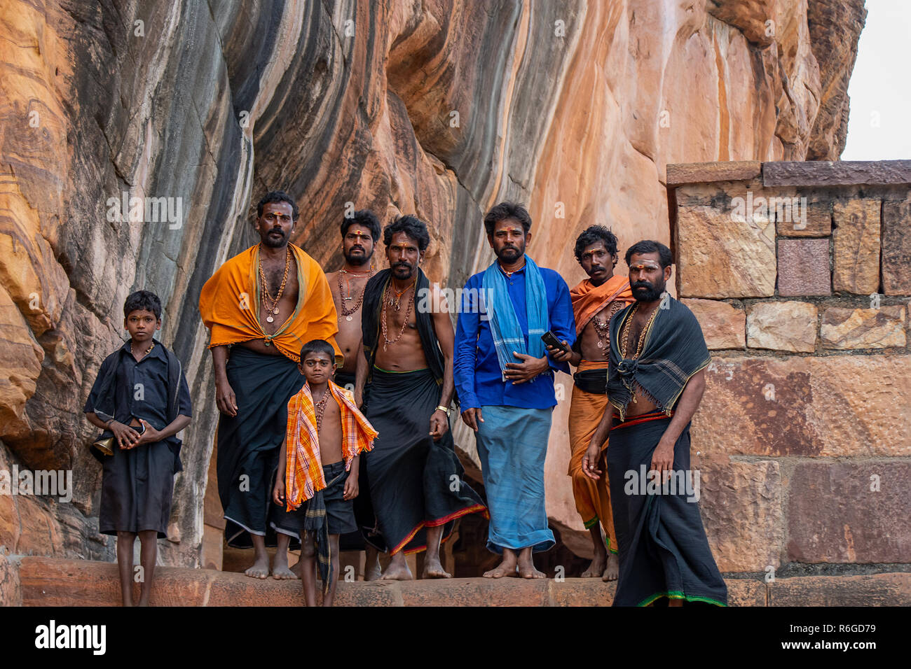 A group of Male Hindu worshipers visit the Hindu cave temples at Badami, India. - Stock Image